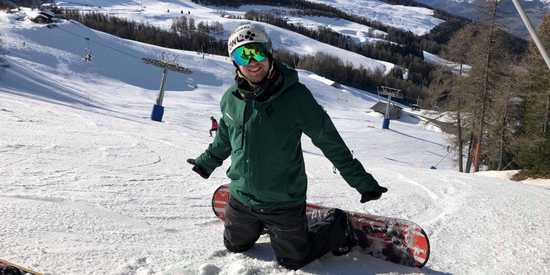 Photo of me kneeling on a snowy ski slope, with a snowboard on my feet. I'm smiling at the camera in full ski kit, my arms are outstretched with two thumbs up.